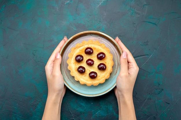 Draufsicht auf cupcake mit kirschen, die jemand serviert