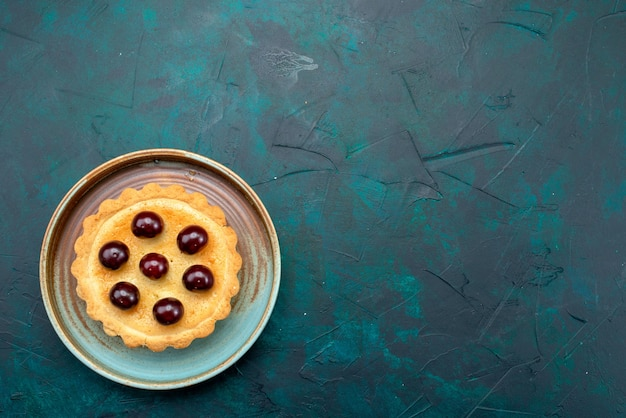 Draufsicht auf cupcake mit kirschen und kühlem teller