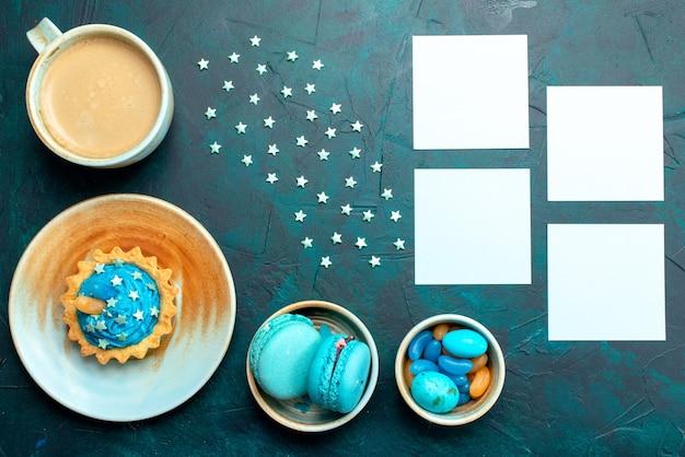 Draufsicht auf cupcake mit sternen neben makronenkaffee und kleinen papieren, um notizen zu machen