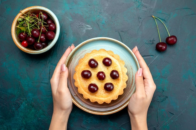 Draufsicht auf cupcake mit verzierten kirschen, die jemand auf tisch legte