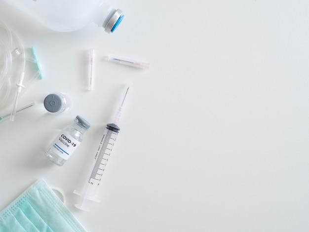 Draufsicht auf das covid-19-impfstoffkonzept mit spritze, medizinischer maske, medizin und reagenzglas