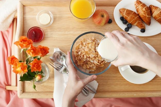 Draufsicht auf das frühstück, das im bett auf holztablett serviert wird