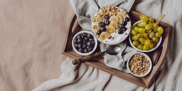 Draufsicht auf das frühstück im bett mit müsli und trauben