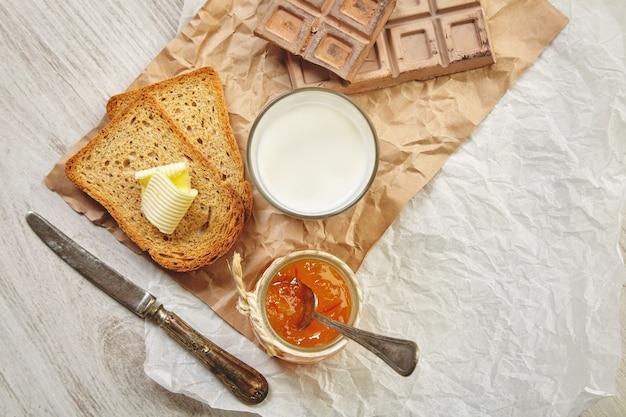 Draufsicht auf das frühstücksset mit schokolade, marmelade, trockenem toastbrot, butter und milch. alles auf bastelpapier und vintage messer und löffel mit patina.