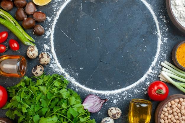 Draufsicht auf das kochen mit eiern, frisches gemüse, gewürze, gefallenes öl, flaschengrün, bündel, gefallenes öl