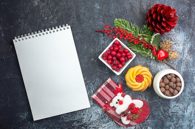 Draufsicht auf das köstliche biskuit-dekorationszubehör des notebooks weihnachtssocke und cornell in einer schüssel tannenzweige auf dunkler oberfläche