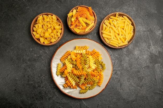 Draufsicht auf das rohprodukt der verschiedenen teigwarenzusammensetzung in den platten auf grauen teigwaren, die rohe teigmahlzeiten kochen?