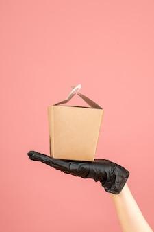 Draufsicht auf das tragen einer schwarzen handschuhhand, die eine kleine schachtel auf pastellfarbenem pfirsich hält