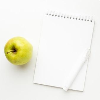 Draufsicht auf das wesentliche des schulanfangs mit apfel und notizbuch