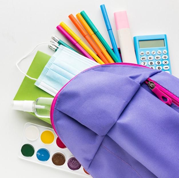 Draufsicht auf das wesentliche für den schulanfang mit rucksack und taschenrechner