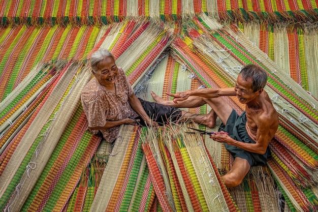 Draufsicht auf den alten vietnamesischen liebhaberhandwerker, der die traditionellen vietnam-matten mit glücksaktion herstellt