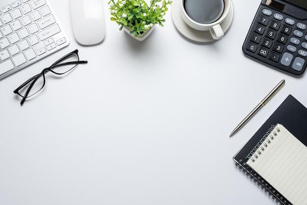 Draufsicht auf den arbeitsbereich eine vielzahl von arbeitsmitteln, die auf einem weißen schreibtischkopierraum platziert sind.