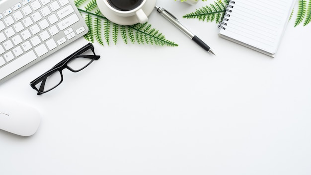 Draufsicht auf den arbeitsbereich tastatur, brille, maus und arbeitsausrüstung sind auf dem schreibtisch platziert.