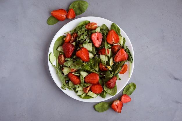 Draufsicht auf den frischen und köstlichen salat aus erdbeeren, gurken, tomaten, spinat, ruccola, bedeckt mit balsamico-sauce auf dem weißen teller. grauer hintergrund. vegetarischer sommersalat.