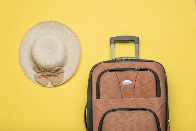 Draufsicht auf den hut einer frau und einen koffer mit einem griff auf gelbem hintergrund. das konzept der sommerreisen. flach liegen.