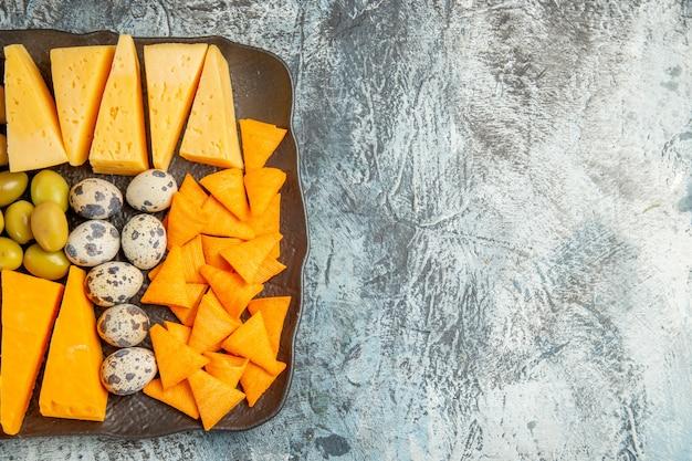 Draufsicht auf den köstlichen besten snack für wein, der auf einem braunen tablett auf der rechten seite auf grauem hintergrund serviert wird