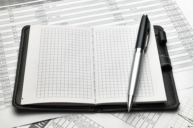 Draufsicht auf den schreibtisch des büroangestellten - leerer notizblock mit leeren seiten und finanzberichten, analyse und buchhaltung