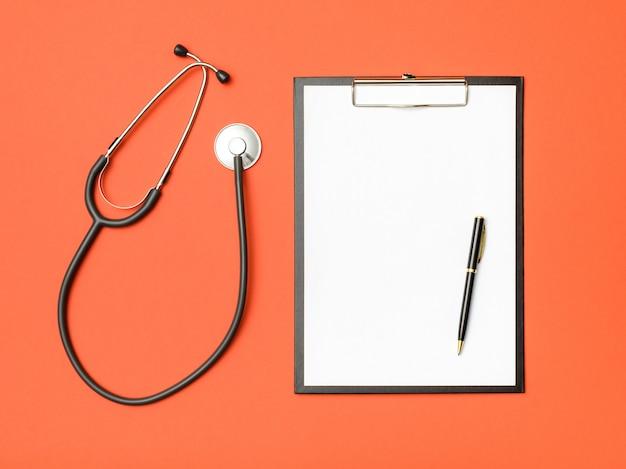 Draufsicht auf den schreibtisch des doktors. stethoskop und notizbuch auf einem farbigen hintergrund
