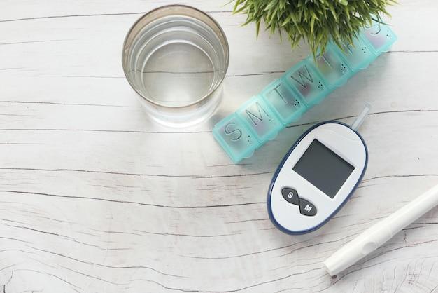 Draufsicht auf diabetische messwerkzeuge und pille auf tisch.
