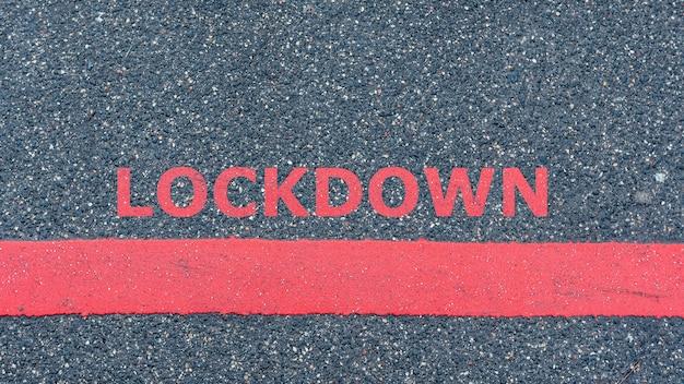 Draufsicht auf die asphaltstraße mit roter linie und text lockdown, restriktions- oder sicherheitswarnkonzept