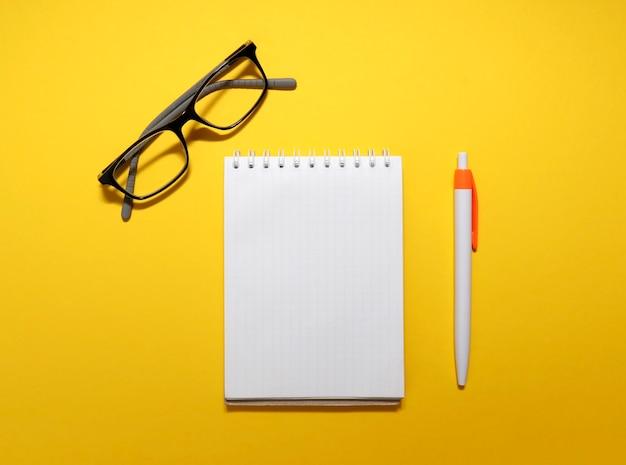 Draufsicht auf die brille, notizblock, stift auf einem leuchtend gelben hintergrund mit platz für text. platz kopieren. geschäft, zweck und geschäftskonzept. arbeitsplatz im büro