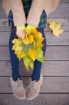 Draufsicht auf die frau, die auf der holzbrücke sitzt und einen schönen haufen gelber ahornblätter hält?