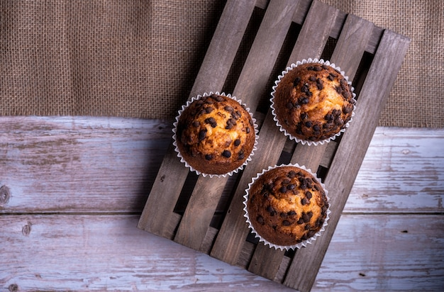 Draufsicht auf die frisch gebackenen cupcakes mit schokoladenstückchen auf einem holztablett wooden