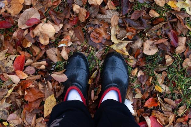 Draufsicht auf die füße in gummischuhen auf dem hintergrund des verwelkten, gefallenen braunen herbstlaubs