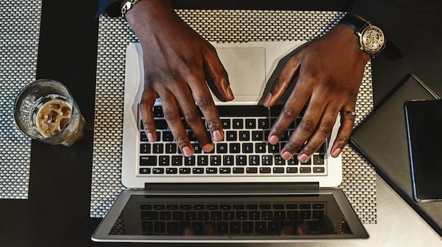Draufsicht auf die hände des mannes, die auf einer tastatur des laptops tippen