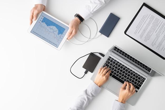 Draufsicht auf die hände von zwei klinikern, die mobile geräte verwenden, während einer von ihnen diagramme analysiert und sein kollege auf laptop schreibt