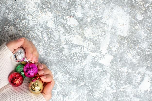 Draufsicht auf die hand, die dekorationszubehör und geschenke für das neue jahr auf der linken seite auf der eisoberfläche hält