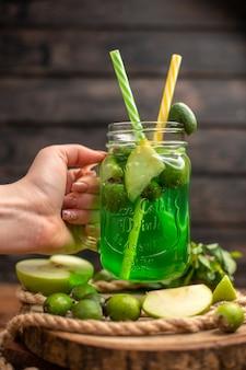 Draufsicht auf die hand, die ein glas mit frischem, köstlichem fruchtsaft hält, serviert mit apfel und feijoas auf einem holzbrett auf einem braunen tisch