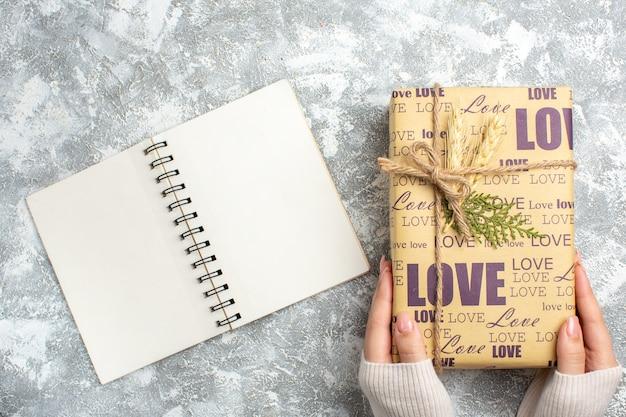Draufsicht auf die hand, die ein großes geschenk für weihnachten und ein offenes notizbuch auf der eisoberfläche hält