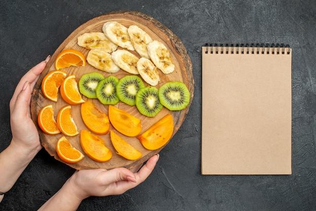 Draufsicht auf die hand, die ein natürliches organisches frisches obst auf einem schneidebrett und ein geschlossenes notizbuch auf dunkler oberfläche hält