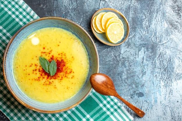 Draufsicht auf die hand, die einen blauen topf mit leckerer suppe mit minze und pfeffer neben gehacktem zitronenholzlöffel auf blauem hintergrund hält