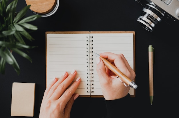 Draufsicht auf die hand einer flachen frau schreibt eine notiz in ein offenes notizbuch, das auf einem schwarzen tisch neben der kamera mit stift und schreibpapier liegt. das konzept der haushaltsbuchhaltung. platz für werbung