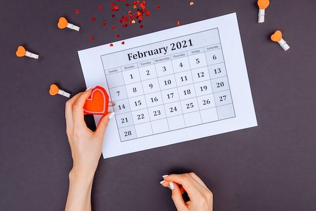 Draufsicht auf die hand einer frau, die ein rotes herz neben dem 14. februar hält. valentinstag konzept