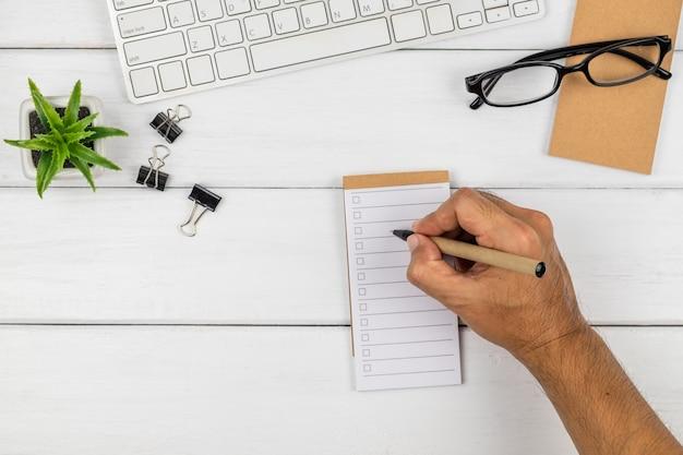 Draufsicht auf die hand eines mannes, die auf checklistenpapier schreibt