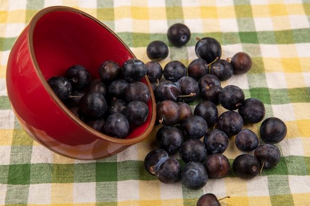 Draufsicht auf die kleinen sauren blau-schwarzen fruchtschollen, die aus einer roten schüssel auf einem karierten tischtuchhintergrund fallen