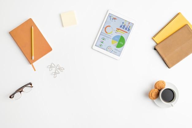 Draufsicht auf die lieferungen von büroangestellten oder maklern, einschließlich notebooks, tablet, brillen, briefpapier, bleistift, tasse kaffee mit keksen und clips