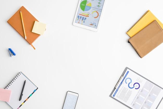 Draufsicht auf die lieferungen von büroangestellten oder maklern - finanzpapiere in der zwischenablage, notizbücher, gadgets, notizpapier, hefter, der den kopierraum umgibt