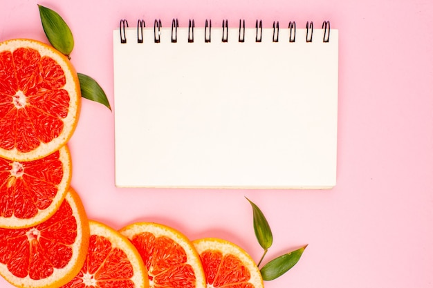 Draufsicht auf die saftigen fruchtscheiben der leckeren grapefruits auf der rosa oberfläche
