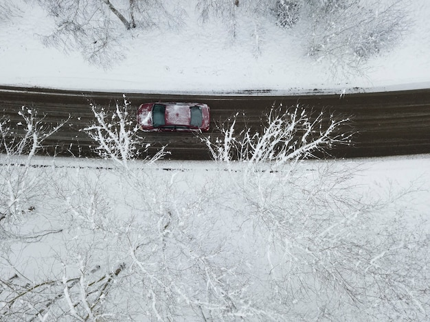Draufsicht auf die straße durch den schneebedeckten wald, auf dem das auto fährt