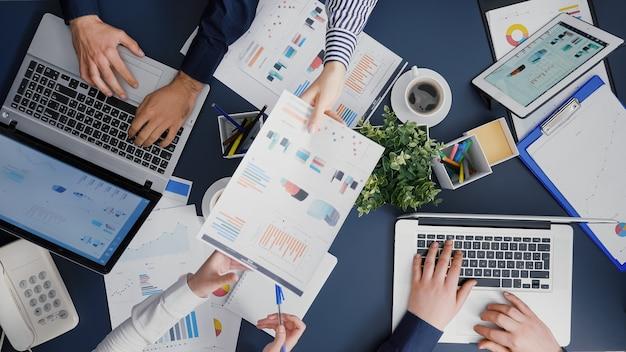 Draufsicht auf die teamarbeit des unternehmens, die am schreibtisch sitzt und investitionen in das management plant