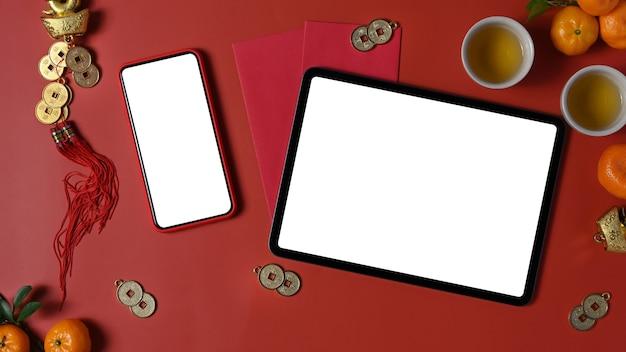 Draufsicht auf digitale tablette, smartphone und zubehör chinese new year festival dekorationen auf rotem hintergrund.