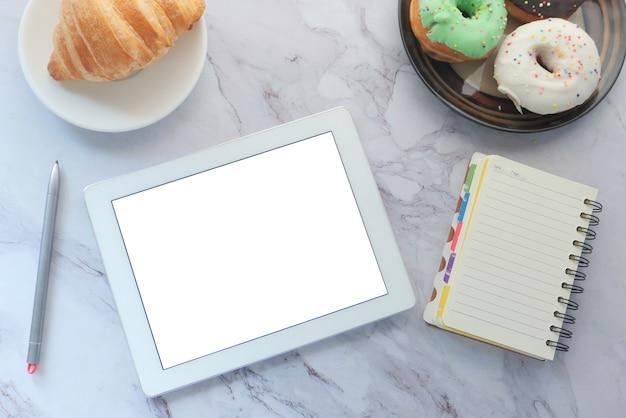 Draufsicht auf digitales tablet, donuts mit lieferanten auf tisch
