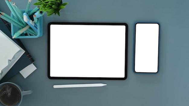 Draufsicht auf digitales tablet, smartphone und bürobedarf auf blauem tisch. leerer bildschirm für ihre textnachricht oder informationsinhalte.