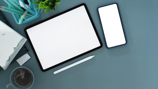 Draufsicht auf digitales tablet, smartphone und stylus-stift auf blauem tisch. leerer bildschirm für ihre textnachricht oder informationsinhalte.
