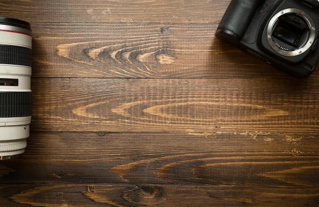 Draufsicht auf digitalkamera und teleobjektiv auf holzhintergrund wooden