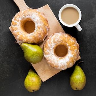 Draufsicht auf donuts auf schneidebrett mit birnen und kaffee